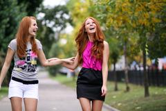 Happy two young women in autumn city Stock Photos