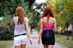 two walking young woman - stock photo