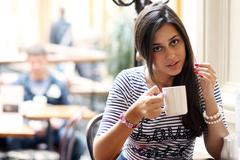 beautiful young girl sipping coffee - stock photo