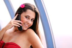 woman in red dress calling by phone - stock photo