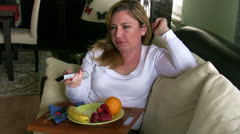 Woman watching tv and eating fruit Stock Footage