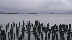 Oil Tanker Ships at Anchor in Columbia River Astoria cloudy with pilings Stock Footage