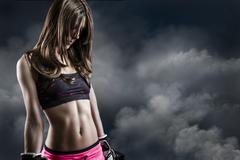 Beautiful woman athlete on cloud background, fitness Stock Photos