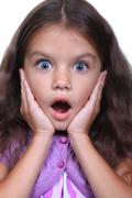 close-up portrait of a little amazing girl with blue eyes and opening mouth i - stock photo