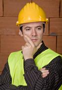 Stock Photo of engineer with yellow hat with a brick wall as background
