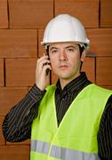 engineer calling with white hat with a brick wall as background - stock photo