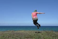 Happy woman with a big jump at the coast Stock Photos