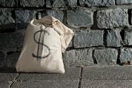 Stock Photo of bag with dollars against a stone wall