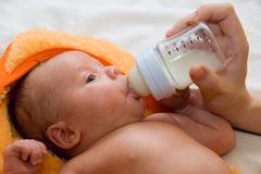 baby boy and feeding bottle - stock photo