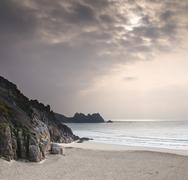 beautiful beach landscape color tinted by sun behind clouds - stock photo
