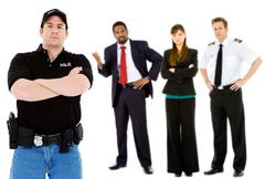 Occupations: serious policeman with others behind Stock Photos