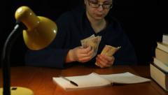Woman in bathrobe counting money at night Stock Footage