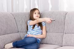 Stock Photo of Cute little girl  watching tv on sofa