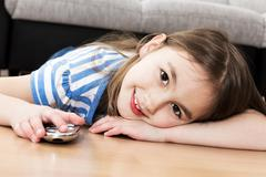 cute little girl holding a remote control - stock photo
