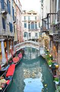 canal in venice with gondolas - stock photo