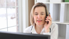 Stock Video Footage of Mature Female Doctor Talking On A Smart Phone Sat At Her Desk  Close Up Portrait