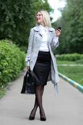 Beautiful young woman business woman in a gray cloak Stock Photos