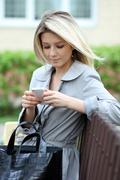 Blonde talking on a cell phone while sitting on a bench Stock Photos