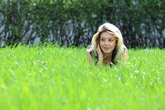 Stock Photo of cute young female lying on grass field at the park