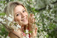 portrait of beautiful blond in spring blossom - stock photo