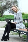 Girl using laptop while sitting on bench at  spring park Stock Photos