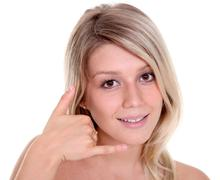 Stock Photo of beautiful woman making a call me gesture