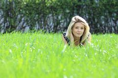 Cute young female lying on grass field at the park Stock Photos