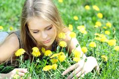 Young woman blows on a dandelion Stock Photos