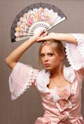 Young woman in a pink dress with a fan in hand Stock Photos