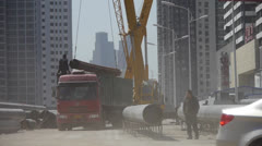 Crane lifting pipes in Construction site,sandstorm. Stock Footage