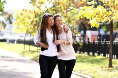 Stock Photo of two cheerful girls twins, in the street