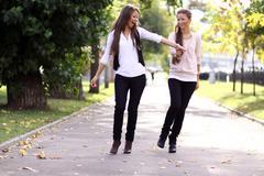fashionable girls twins walk in the street - stock photo