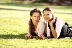 Stock Photo of young beautiful twins of sister lays on green field
