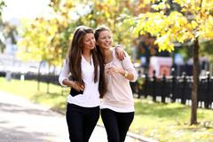 two cheerful girls twins, in the street - stock photo