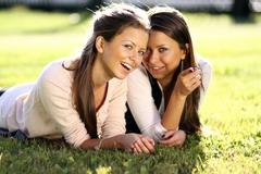 Young beautiful twins of sister lays on green field Stock Photos