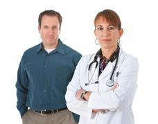 Doctor: serious doctor with patient behind Stock Photos