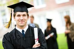 graduation: cheerful graduate with diploma - stock photo