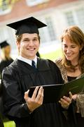 Graduation: recent graduate stands with mother Stock Photos