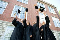 graduation: graduates toss caps in air - stock photo