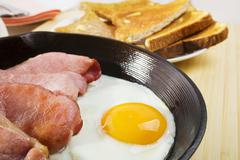 Egg and bacon in a cast iron skillet Stock Photos