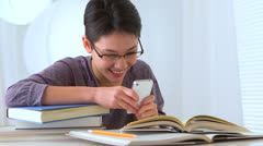 Mixed race Asian woman with smart phone and books Stock Footage