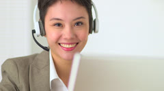 Asian customer service representative with headset in call center - stock footage