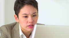 Unhappy Asian businesswoman working on laptop - stock footage