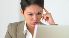 Asian Business woman concentrating while working on laptop Stock Footage