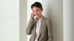Happy Asian business woman talking on mobile phone - stock footage