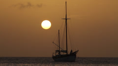 Sunset off coast - Sailboat anchored while another goes through frame Stock Footage