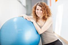 young woman doing exercise with a gym ball - stock photo