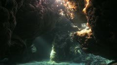 camera travels in the cave with sun beam coming through - stock footage