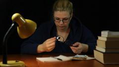 Woman in bathrobe looking at eyeglasses Stock Footage
