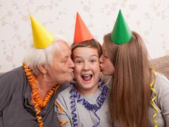 the elderly woman and the girl kiss in a cheek of the boy, congratulating him - stock photo
